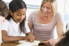 Uma estudante e sua leitura do professor na classe Imagens de Stock Royalty Free