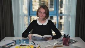 Uma estudante feliz toma o livro da tabela e começa-o lê-la Fazendo trabalhos de casa Sorriso na câmera filme