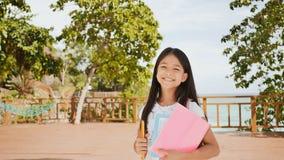 Uma estudante filipina encantador com uma trouxa e os livros em um parque fora da costa A da menina das poses alegremente, aument imagens de stock royalty free