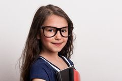 Uma estudante pequena com os vidros e o uniforme que estão em um estúdio, guardando o bloco de notas Imagem de Stock Royalty Free