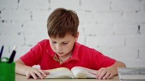 Uma estudante que lê um livro de texto video estoque