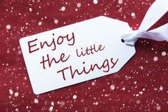 Uma etiqueta no fundo vermelho, flocos de neve, citações aprecia coisas pequenas foto de stock royalty free