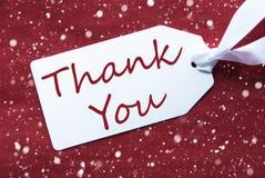 Uma etiqueta no fundo vermelho, flocos de neve, texto agradece-lhe imagens de stock