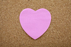 Uma etiqueta pegajosa do coração em um quadro de mensagens Foto de Stock Royalty Free