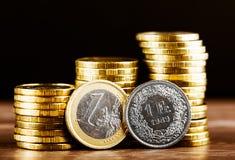 Uma euro- moeda e um dinheiro suíço da franquia e do ouro fotografia de stock royalty free