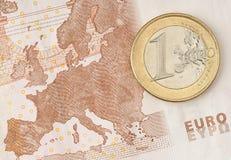 Uma euro- moeda na euro- nota de banco Fotos de Stock Royalty Free