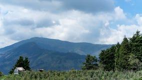 Uma exploração agrícola com um fundo da montanha imagens de stock royalty free