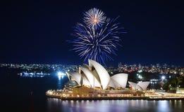 Uma exposição impressionante dos fogos-de-artifício ilumina acima o céu em azul e em branco sobre Sydney Opera House imagem de stock royalty free