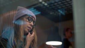Uma fêmea à moda do moderno nos vidros que fala no café bebendo do telefone em um café vídeos de arquivo
