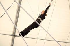 Uma fêmea adulta pendura em um trapézio de voo em um gym interno A mulher é um artista de trapézio amador fotografia de stock royalty free