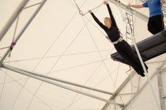 Uma fêmea adulta pendura em um trapézio de voo em um gym interno A mulher é um artista de trapézio amador imagem de stock royalty free