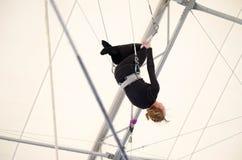Uma fêmea adulta pendura em um trapézio de voo em um gym interno A mulher é um artista de trapézio amador fotos de stock royalty free