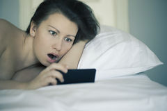 Uma fêmea bonita encontra-se na cama e não se pode cair adormecido e não se lê a notícia no smartphone insomnia psychology phobia Fotografia de Stock Royalty Free