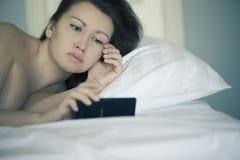 Uma fêmea bonita encontra-se na cama e não se pode cair adormecido e não se lê a notícia no smartphone insomnia psychology phobia Fotografia de Stock