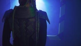 Uma fêmea com dreadlocks longos está vestindo a armadura do metal e está estando na frente da vigia da nave espacial, 4k filme