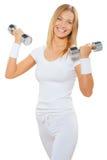 Uma fêmea da aptidão que guarda dois pesos e sorrisos Fotografia de Stock