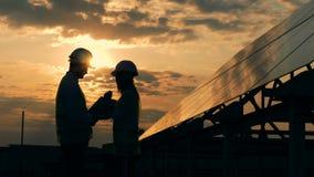 Uma fêmea e um homem projetam a fala nos raios do sol de ajuste perto de um painel solar Conceito da energia alternativa vídeos de arquivo