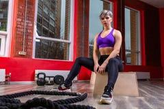 Uma fêmea loura nova atlética e feliz que levanta com cordas de formação atheltic em um gym fotos de stock