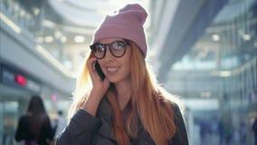 Uma fêmea nova do moderno está falando no telefone na alameda grande foto de stock royalty free