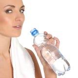 Uma fêmea nova está bebendo a água de refrescamento Imagens de Stock