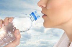 Uma fêmea nova está bebendo a água de refrescamento Imagens de Stock Royalty Free