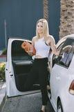 Uma fêmea nova que leva uma ioga Mat Exits Her Car e está feliz imagens de stock royalty free