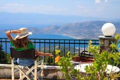 Uma fêmea que senta-se em um balcão do terraço em um recurso de verão que negligencia o mar fotos de stock royalty free