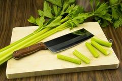 Uma faca de cozinha e um aipo fresco na placa Imagens de Stock Royalty Free