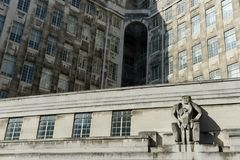 Uma fachada da construção com uma escultura de um homem e de uma criança Fotografia de Stock