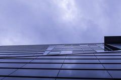 Uma fachada de vidro abaixo de um céu nebuloso imagens de stock royalty free