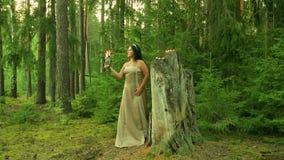 Uma fada da floresta está em um grande coto com velas e guarda um castiçal com velas ardentes em sua mão filme