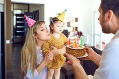 Uma família com um bolo felicita uma criança feliz em seu aniversário fotos de stock