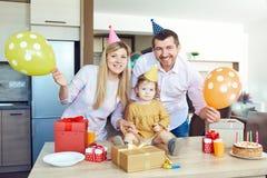 Uma família com um bolo felicita uma criança feliz em seu aniversário imagens de stock royalty free