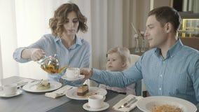 Uma família com uma criança pequena em um restaurante: paizinho, mamã e filha filme