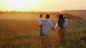 Uma família de cultivo nova com crianças vai encontrar o sol vídeos de arquivo