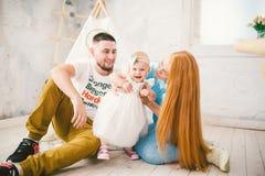 Uma família de três feliz Mamã, paizinho, menina do bebê de um ano da criança no jogo do vestido, riso, sorriso na sala brilhante fotografia de stock