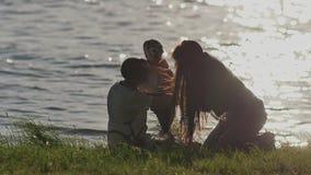 Uma família de três nova no lago nos raios do por do sol Uma noite ensolarada no parque Pais com filha dad video estoque