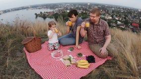 Uma família de três povos, de paizinhos da mamã e de um bebê em um piquenique durante o fim de semana filme