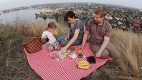Uma família de três povos, de paizinhos da mamã e de um bebê em um piquenique durante o fim de semana video estoque