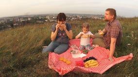 Uma família de três povos, de paizinhos da mamã e de um bebê em um piquenique durante o fim de semana vídeos de arquivo