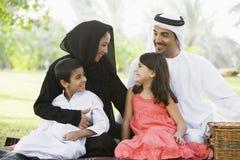 Uma família do Oriente Médio que senta-se em um parque Fotografia de Stock Royalty Free