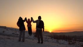 Uma família feliz, de três povos, está em uma montanha no inverno video estoque