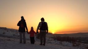 Uma família feliz, de três povos, está em uma montanha no inverno filme