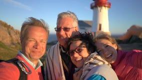 Uma família feliz grande toma um selfie ou usa o telefone a câmera video da chamada no seacoast com um farol velho filme