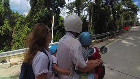 Uma família feliz monta um velomotor nos trópicos video estoque