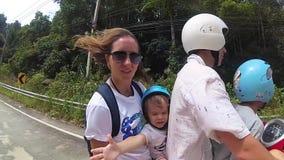 Uma família feliz monta um velomotor nos trópicos filme