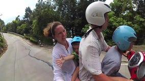 Uma família feliz monta um velomotor nos trópicos vídeos de arquivo