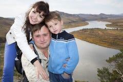 Uma família feliz na montanha que negligencia a corrente sob Imagem de Stock