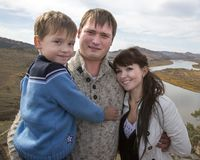 Uma família feliz na montanha que negligencia a corrente sob Foto de Stock Royalty Free