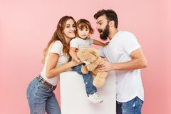 Uma família feliz no fundo cor-de-rosa imagem de stock royalty free